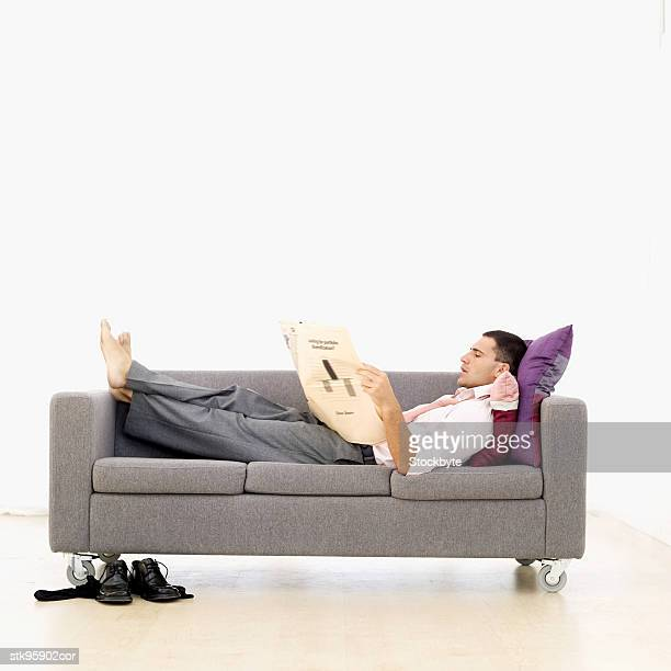 businessman lying on a sofa and reading a newspaper
