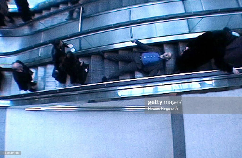 Businessman lying on escalator, elevated view (video still) : Stock Photo