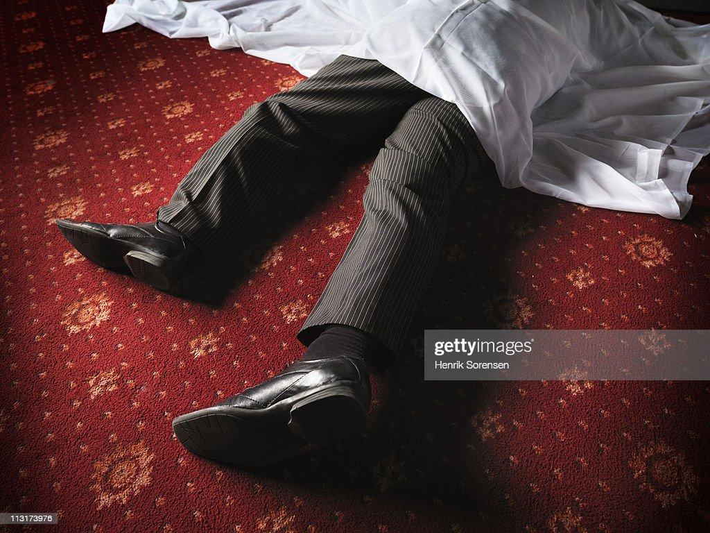 Businessman lying on floor under a white sheet