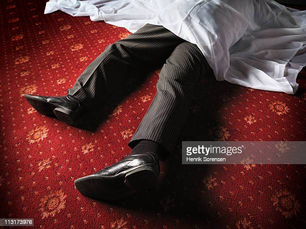 Businessman lying on floor under a white sheet