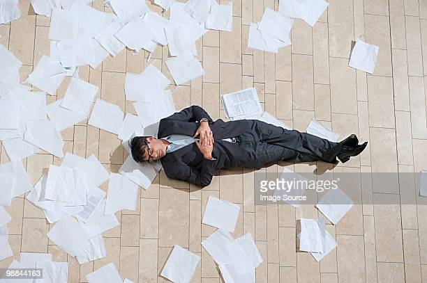 Businessman lying on floor with scattered papers