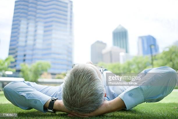 Businessman lying on grass, hands behind head