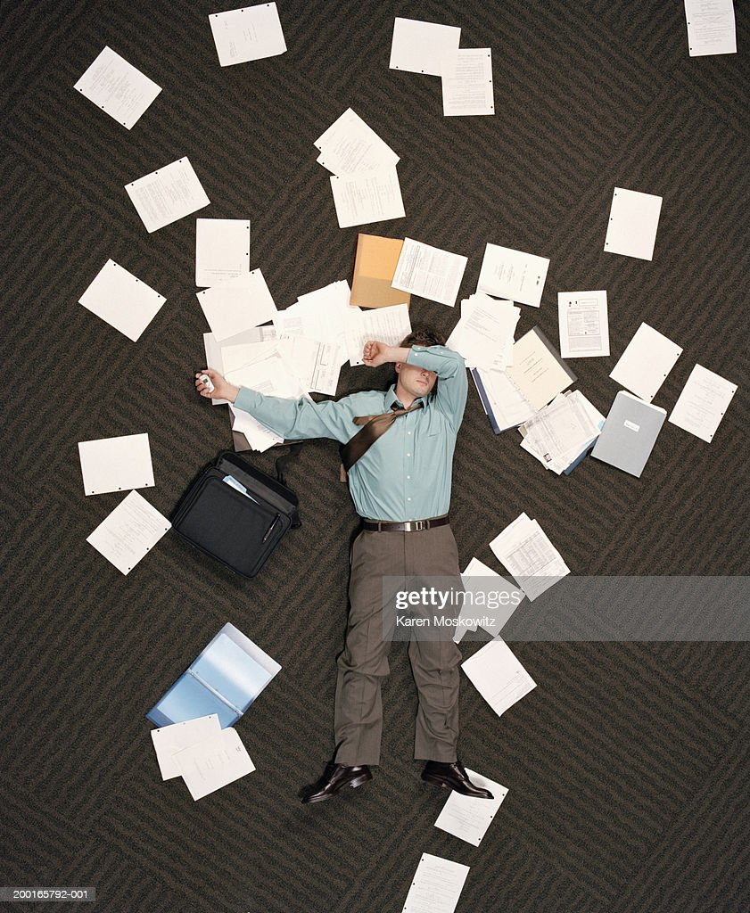 Businessman lying on ground littered with paper, overhead view : Stock Photo