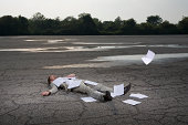 Businessman lying on ground under fallen papers (composite)