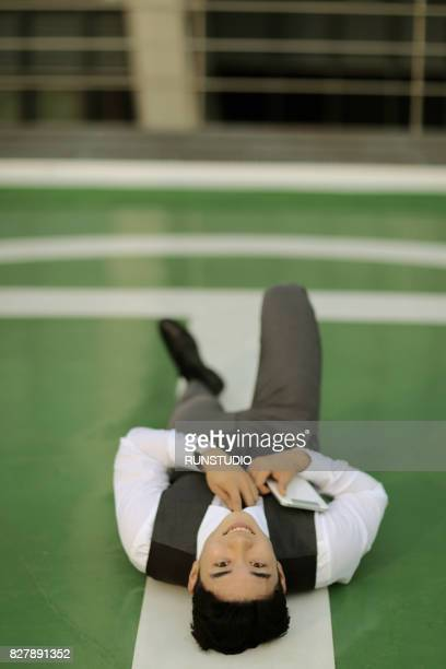 Businessman lying on helicopter landing pad