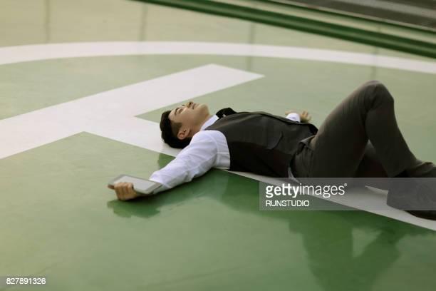 Businessman lying on helipad