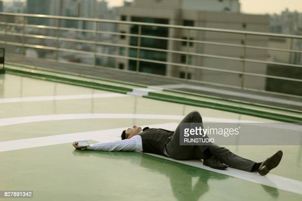 Businessman lying on rooftop