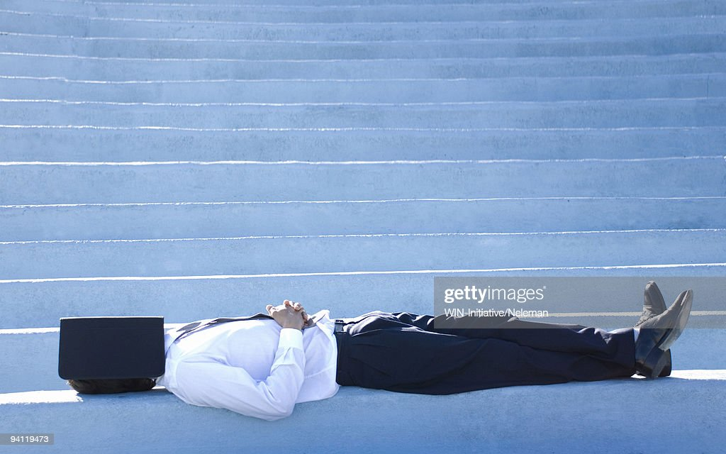 Businessman lying on steps with his face covered with a notebook, Montevideo, Uruguay : Stock Photo
