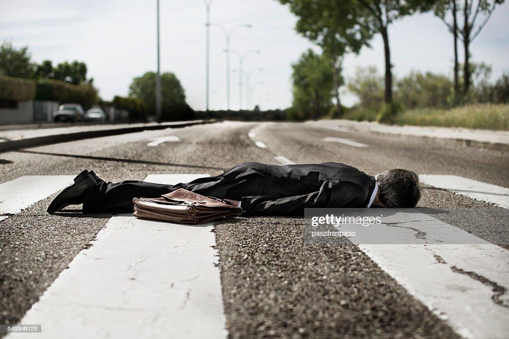 Businessman lying on zebra crossing.