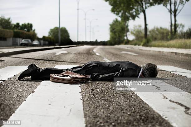 Businessman lying on zebra crossing.