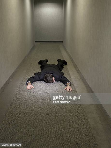 Businessman lying outstretched on corridor floor, rear view