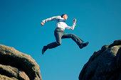 Businessman Makes a Blue Sky Leap Between Boulders
