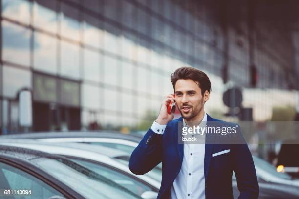 Businessman making a phone call at airport parking lot