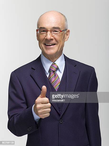 Businessman showing thumbs up sign, smiling, portrait, close-up