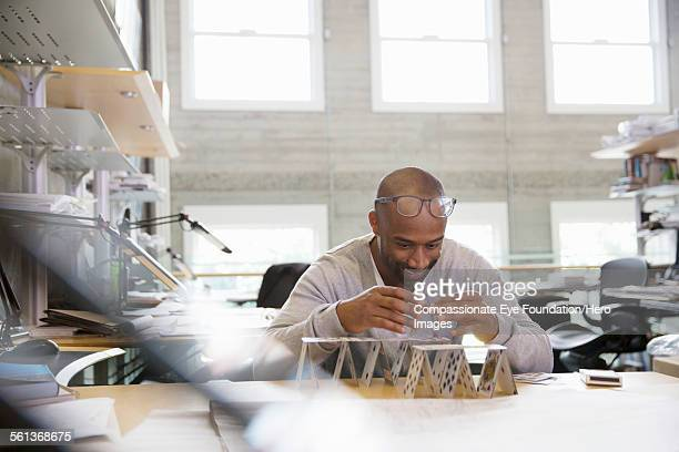 Businessman making house of cards in office