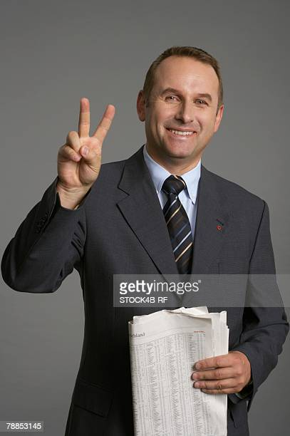 Businessman making peace sign