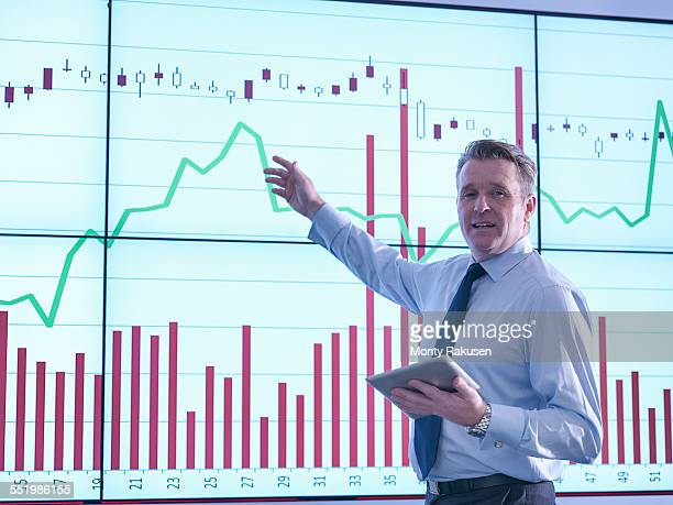Businessman making presentation in front of graphs on screen, portrait
