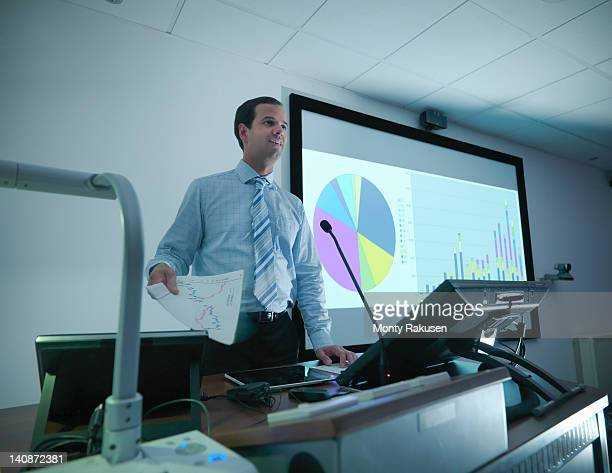 Businessman making presentation on screen in conference room