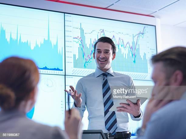 Businessman making presentation to colleagues in front of graphs on screen