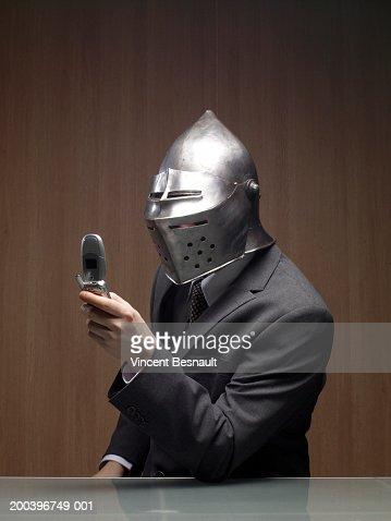 Businessman man wearing knight helmet, holding mobile phone