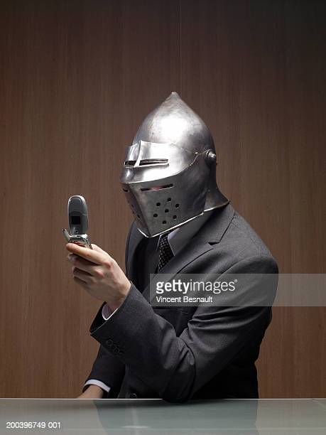 Businessman man wearing knight helmet, holding mobile phone