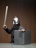 Businessman man wearing knight helmet, using laptop as shield