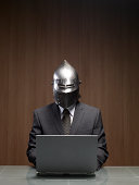 Businessman man wearing knight helmet, using laptop