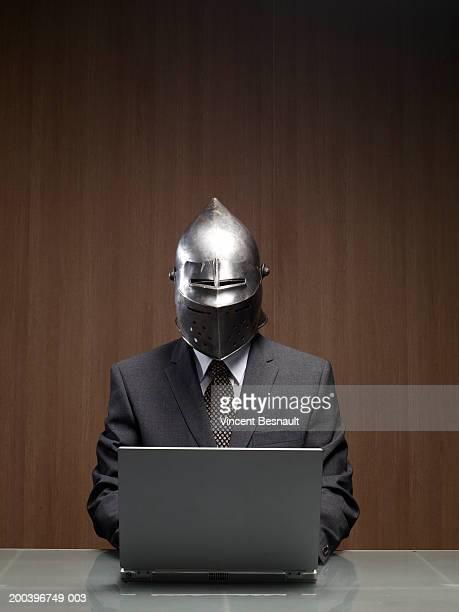 Businessman man wearing knight helmet, using laptop