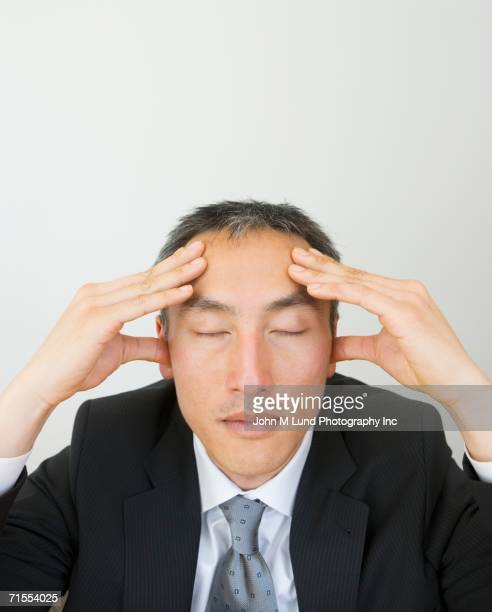 Businessman massaging temples with eyes closed