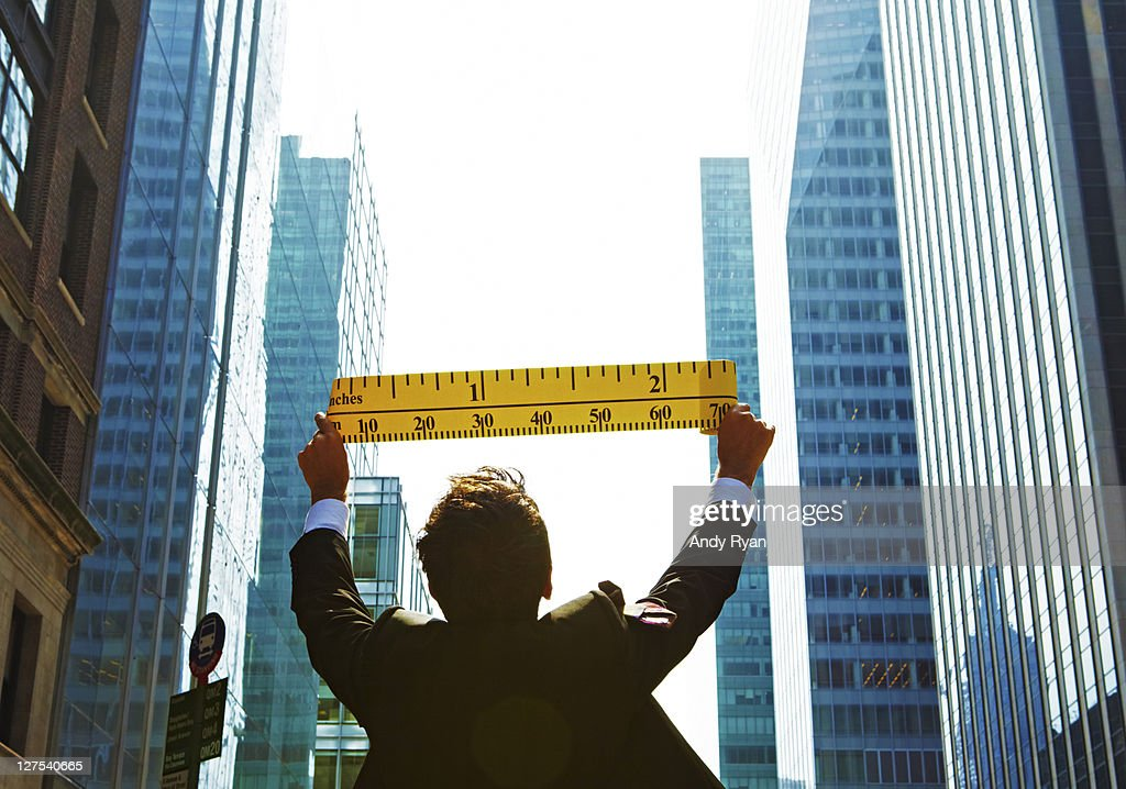 Businessman measuring city buildings with tape. : Stock Photo