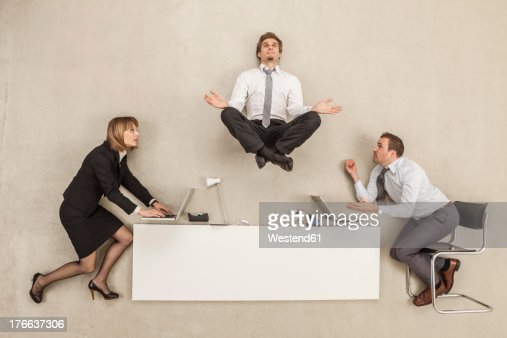 Businessman meditating above office desk while others working