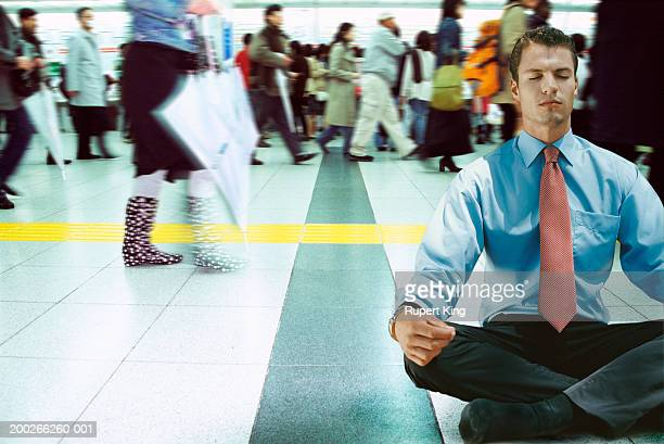 Businessman meditating in busy concourse (Digital Composite)
