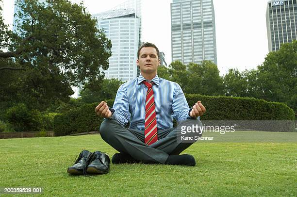 Businessman meditating in park