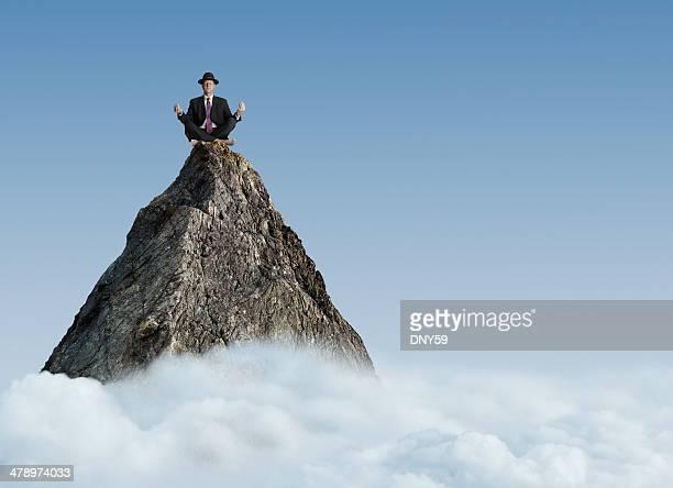 Empresario Meditando en la cima de una montaña del pico