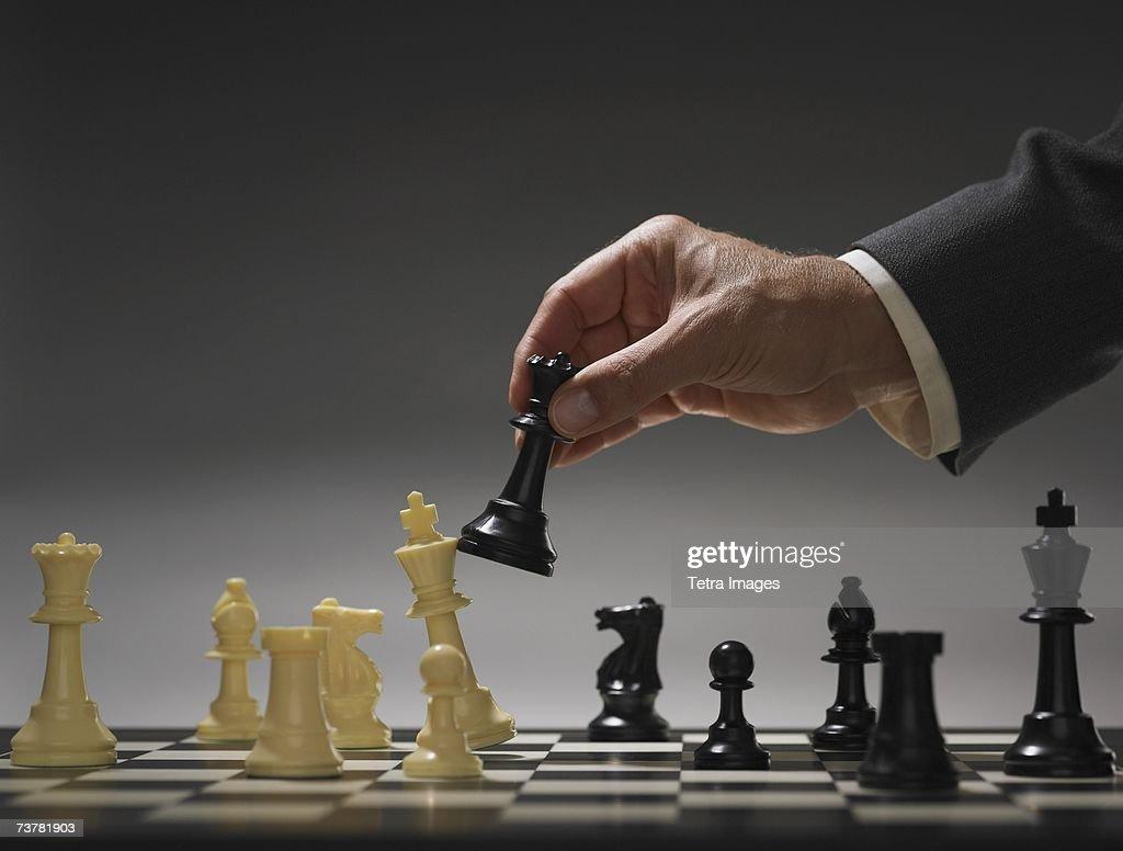 Businessman moving chess piece