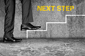 Low section view of a businessman climbing on stairs representing the concept of successful business.