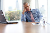 Businessman napping at desk in office