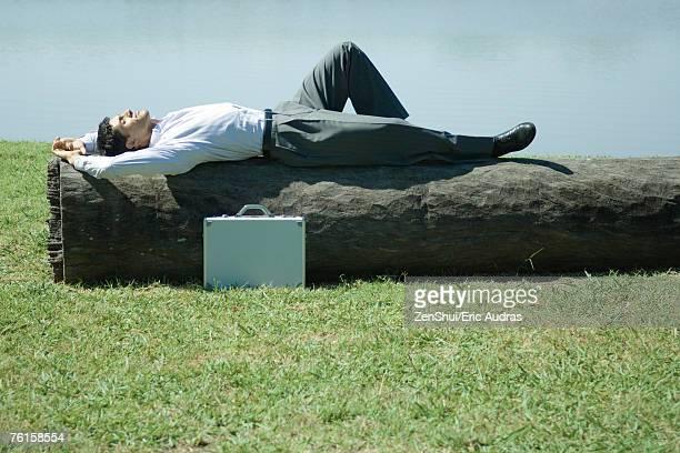 Businessman napping on log