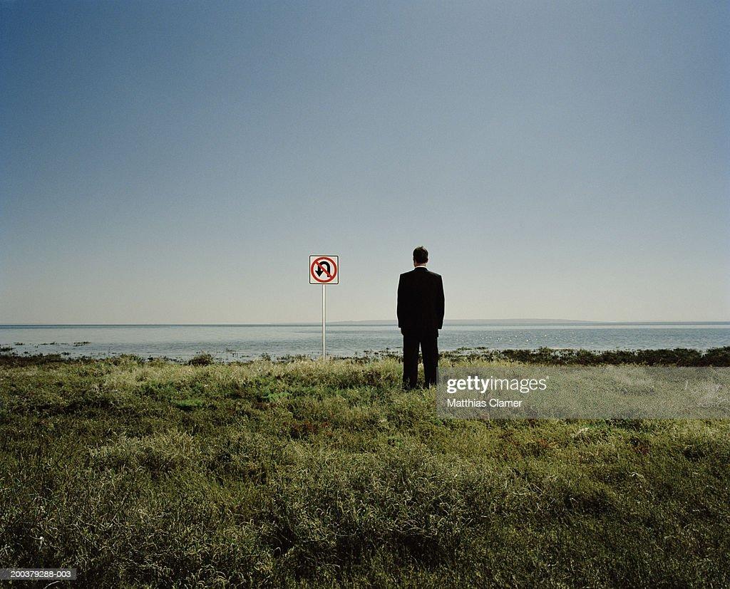 Businessman near 'No U-turn' sign near ocean, rear view : Stock Photo