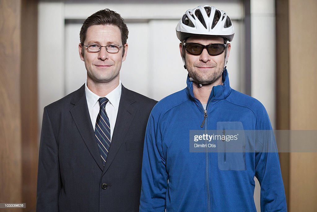 Businessman next to himself dressed as a cyclist : Stock Photo