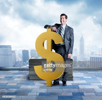 Businessman Next To Large Dollar Sign With Stack Of Money