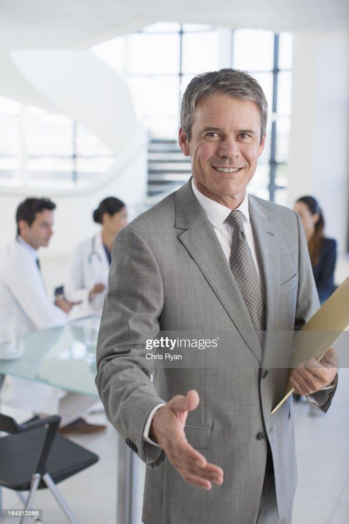 businessman offering handshake in meeting stock photo