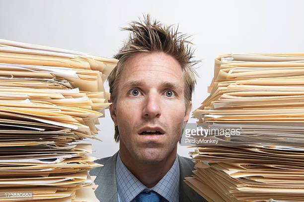 Businessman Office Worker Sits Dazed Between Piles of Paperwork Files