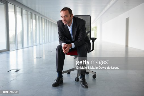 Businessman on a chair, in empty office : Stock Photo