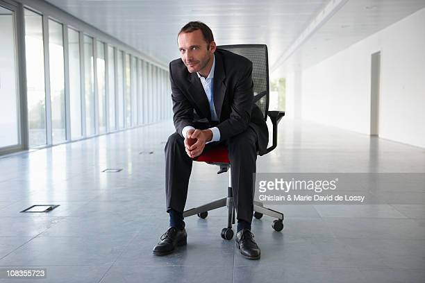 Businessman on a chair, in empty office