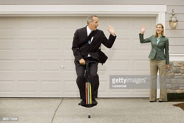Businessman on a pogo stick waving at a businesswoman