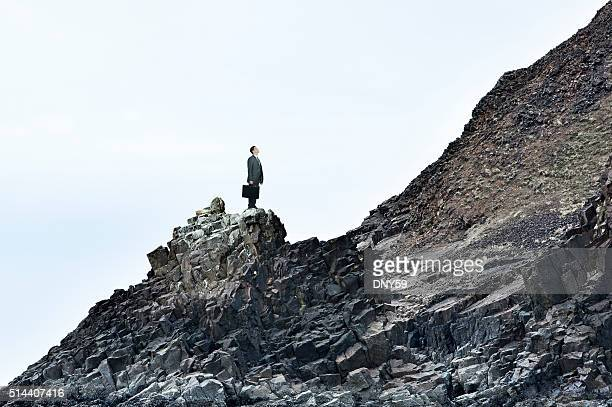 Businessman On A Rocky Slope Looks At The Challenges Ahead