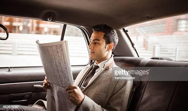 Geschäftsmann auf ein yellow cab liest Zeitung
