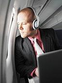 Businessman on aeroplane, wearing headphones, looking out of window