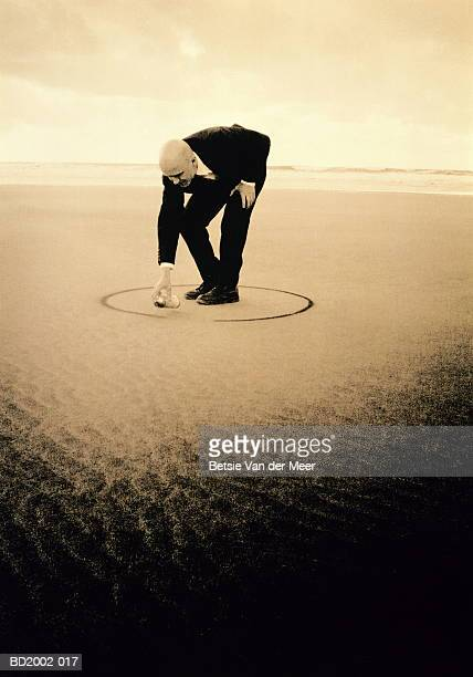 Businessman on beach, drawing circle around feet (toned B&W)